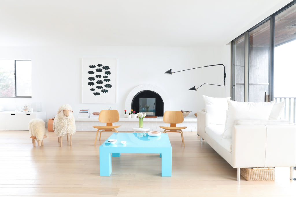 Modern, minimalist living room with blue coffee table, sheep, artwork, wood floors in Faunamade blog post