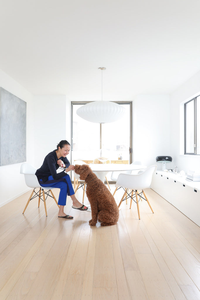 Artist Tina Frey and standard poodle dog in modern dining room on wood floors in Faunamade blog post