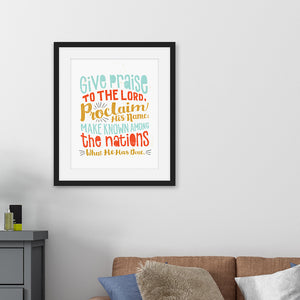 "Framed artwork in a black frame on a wall above a sofa featuring a white paper print with colorful lettering with the Bible verse Psalm 105:1 ""Give praise to the Lord, proclaim his name; make known among the nations what he has done."""