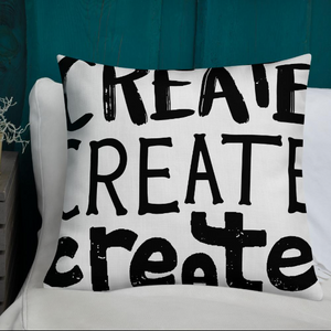 "A pillow on a bed with the phrase ""create, create, create"" in black lettering. The pillow is white."