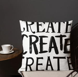 "A pillow on a chair with a coffee mug on a table next to it. The white pillow features the phrase ""create, create, create"" in black lettering with each word in three different fonts."