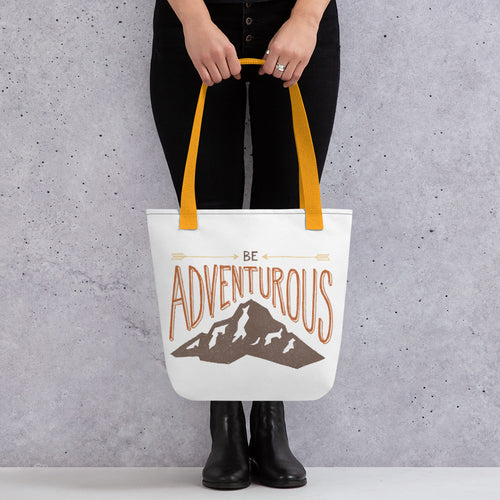 "A woman holding a tote bag with yellow handles and the tote bag is a white/off white color. The design of the quote ""Be Adventurous"" with arrows pointing to the word ""be"" and a mountain illustration underneath the word ""adventure."""