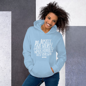 A woman wearing a light blue hoodie with the Bible verse words Do justly, love mercy, walk humbly, with your God, Micah 6:8 in white lettering.