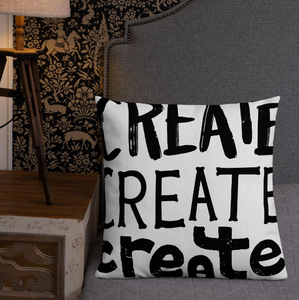 "A pillow leaning on a grey bed headboard. The white pillow features the phrase ""create, create, create"" in black lettering with each word in three different fonts."