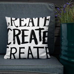 "A pillow leaning on a grey sofa with a plant in the background. The white pillow features the phrase ""create create create"" in black letters."