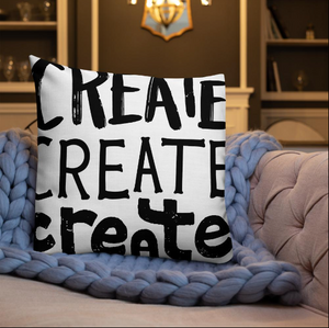 "A pillow on a sofa with a blue knitted blanket with the phrase ""create, create, create"" in black lettering with each word in three different fonts."