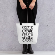 "Load image into Gallery viewer, Someone holding a tote bag with black handles and a white fabric bag. The lettering is in black and features the words ""create, create, create, create, create"" with each word in a different hand lettered font."