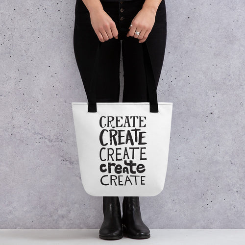 Someone holding a tote bag with black handles and a white fabric bag. The lettering is in black and features the words