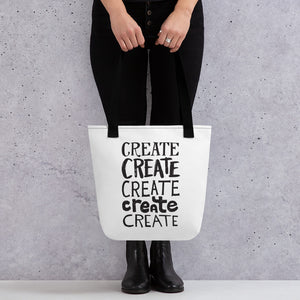 "Someone holding a tote bag with black handles and a white fabric bag. The lettering is in black and features the words ""create, create, create, create, create"" with each word in a different hand lettered font."
