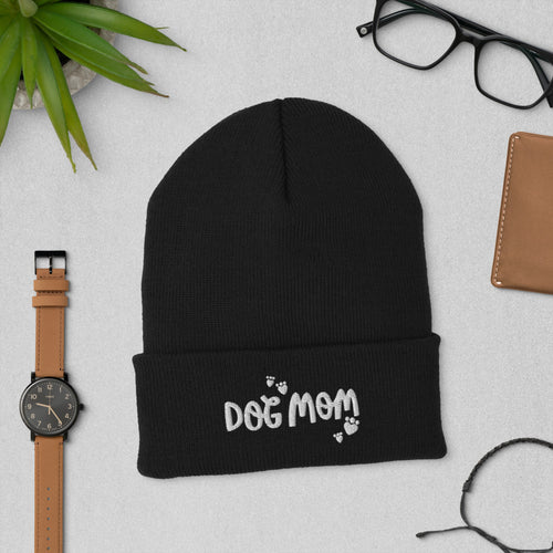 A black colored winter beanie hat with Dog Mom featured on the cuff of the hat. Small hearts in the shape of paws are around the Dog Mom words. This makes a fun gift for any dog mom you know.