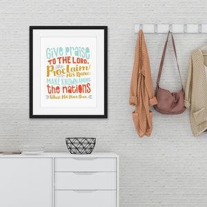 "Hand drawn lettering artwork in a black frame over a chest of drawers. The artwork has the Bible verse Psalm 105:1 ""Give praise to the Lord, proclaim his name; make known among the nations what he has done."""