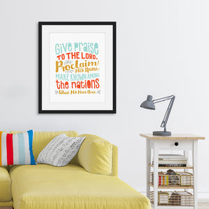 "Lettering artwork is featured in a black frame above a sofa. The artwork has the Bible verse Psalm 105:1 ""Give praise to the Lord, proclaim his name; make known among the nations what he has done."""