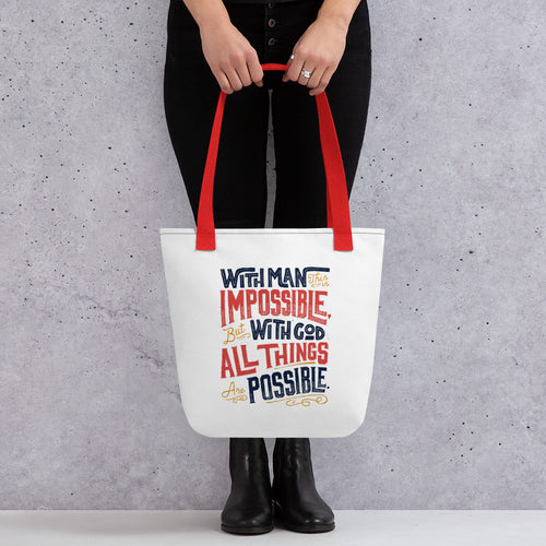 Someone holding a tote bag with red handles and a white fabric bag. The artwork features the Matthew 19:26 Bible verse reading
