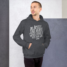 Load image into Gallery viewer, A man wearing dark grey hoodie with the Bible verse words Do justly, love mercy, walk humbly, with your God, Micah 6:8 in white lettering.