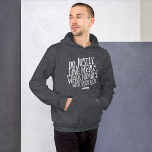 A man wearing dark grey hoodie with the Bible verse words Do justly, love mercy, walk humbly, with your God, Micah 6:8 in white lettering.