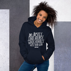 A woman wearing a navy hoodie with the Bible verse words Do justly, love mercy, walk humbly, with your God, Micah 6:8 in white lettering.