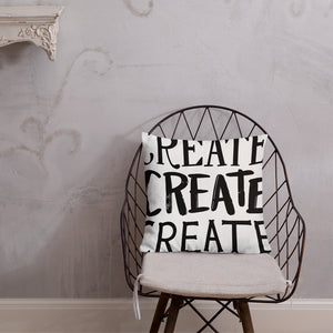 "A pillow on a chair against a grey wall. The pillow is white and features the words ""create, create, create"" in black lettering with each word in three different fonts."