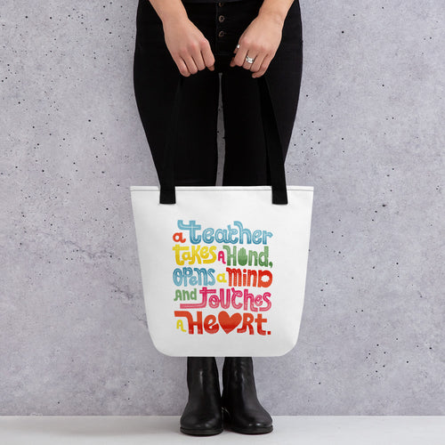 "A woman holding a tote bag with black handles and the tote bag is a white/off white color. The design of the quote ""A teacher takes a hand, opens a mind, and touches a heart"" is featured on the bag. The ""a"" in the word ""heart"" is a heart shape and the words are blue, red, yellow and green."