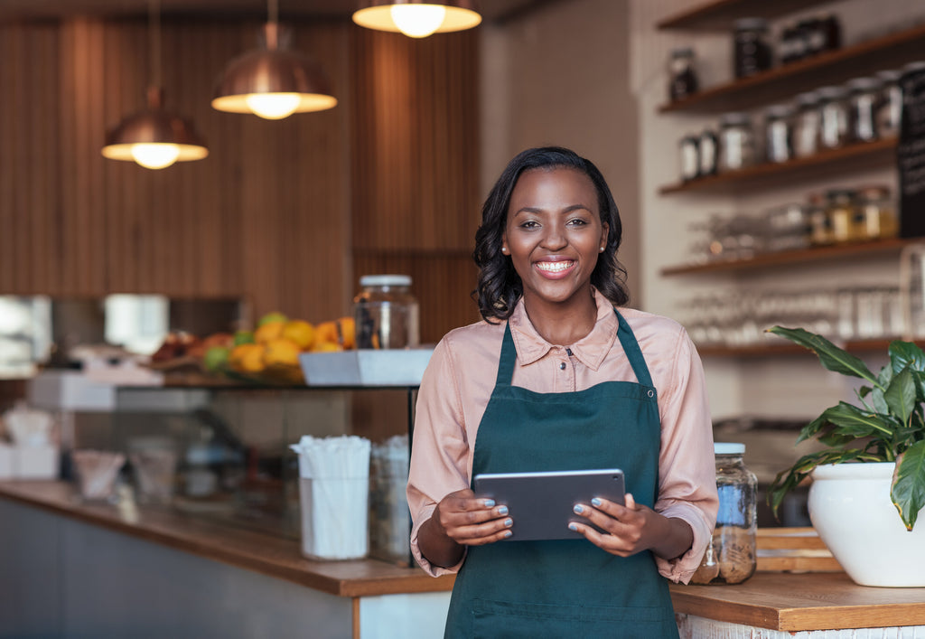 Smiling Woman at Counter with Tablet