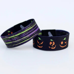 Halloween wristband with Pumpkin faces and beetlejuice colors on the reverse
