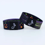 Load image into Gallery viewer, Wristband with jack-o-lantern pumpkins and green purple black brush stroke on the reverse