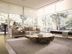 Woman relaxing on the couch in a beautiful living room with floor to ceiling windows with motorized shades opened