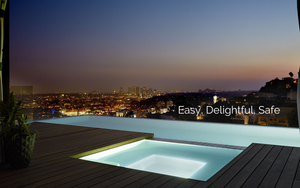 Infinity pool in evening with custom lighting overlooking city
