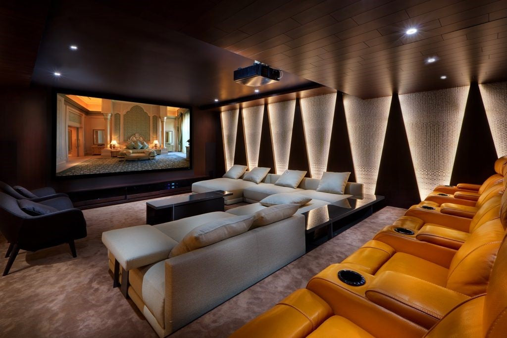 Custom home theater with large screen, couches and theater style leather seats and lighting.
