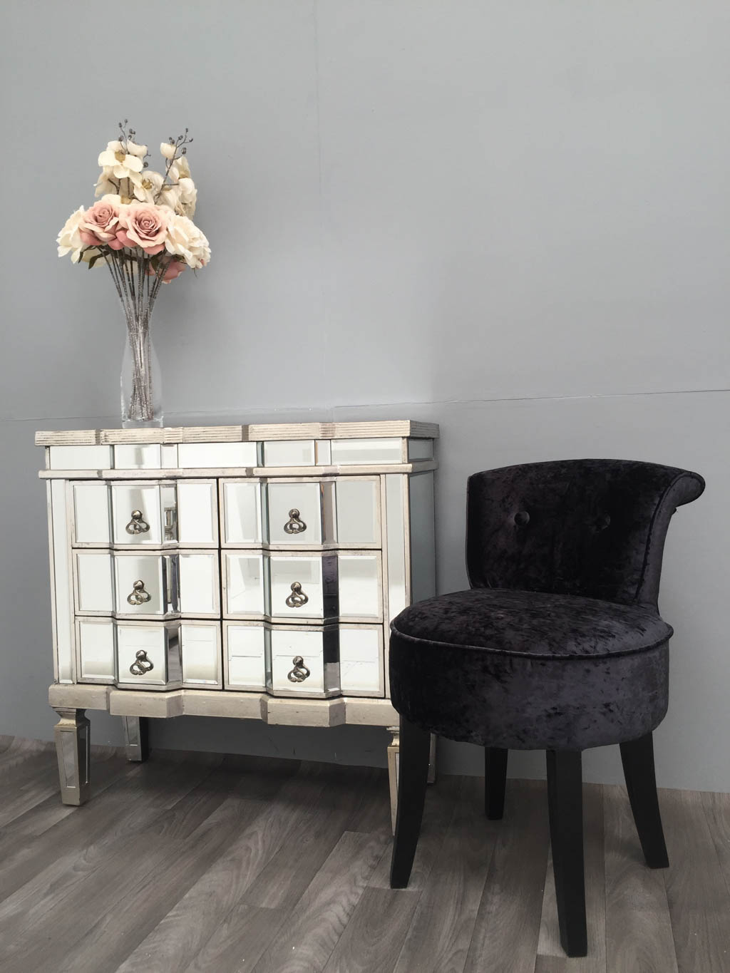 Charleston 6 Drawer Mirrored Chest arranged next to a black chair on the right