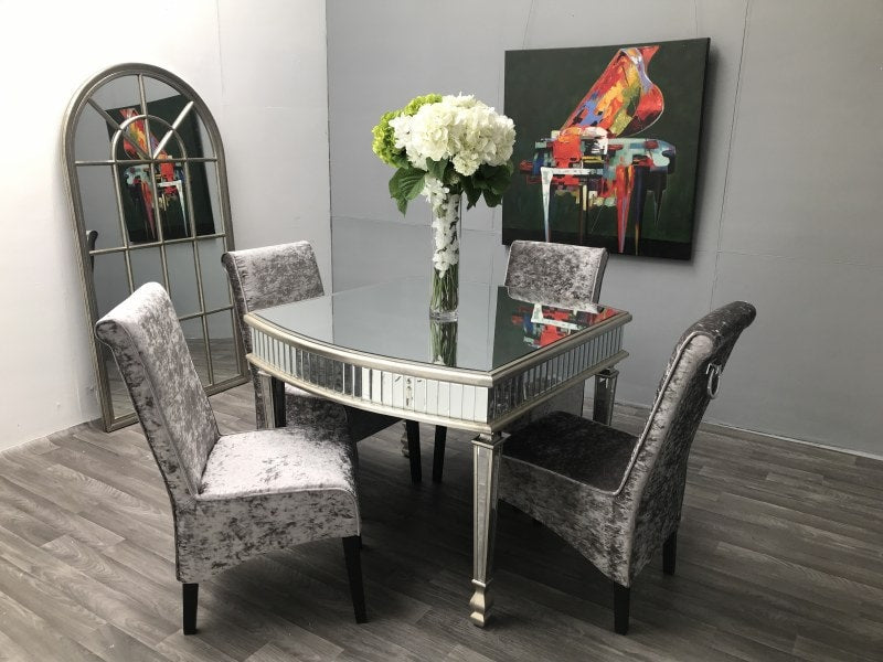 Mirrored dining table with four chairs arranged around it. Vase with flowers was placed on the top of the table.