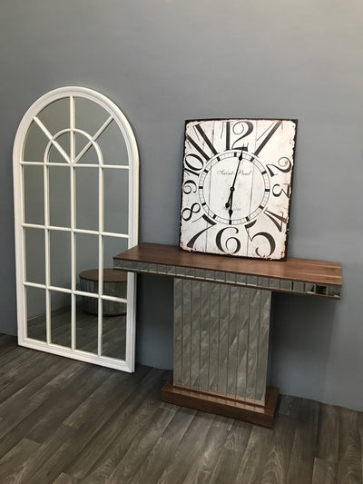 Mirrored Console Table with Walnut Wooden Top arranged with wall clock on top standing to a white window mirror on the left