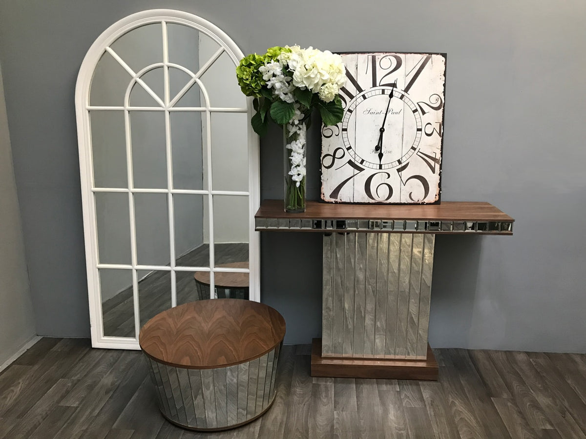 Mirrored Side Table with Walnut Wooden Top and vase of white and green flowers. A rectangle antiqued mirror is placed on top leaning on a wall behind it.