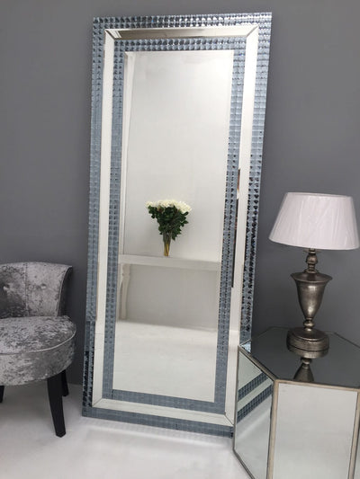 Hollywood Leaner Mirror arranged on the grey wall background. Grey velvet chair standing on it's left with lamp placed on top of mirrored side table standing to the right side of the mirror