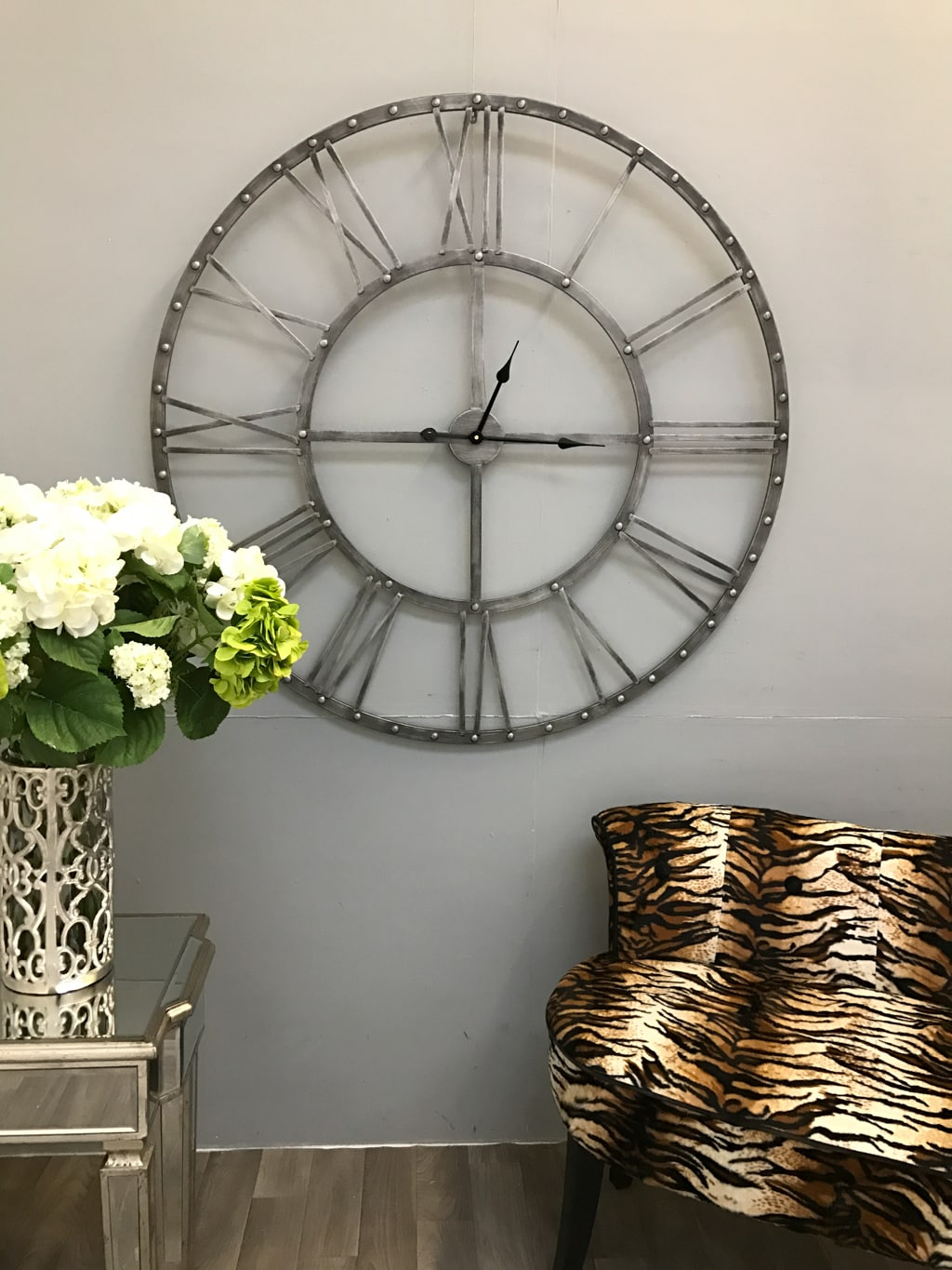 Round Skeleton Wall Clock in Antiqued Silver hanging on a grey wall