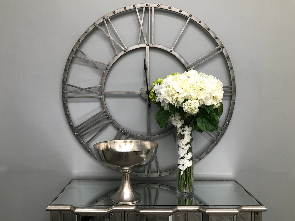 Silver Bowl On Stand, arranged on a side table by a tall vase holding white flowers. Large skeleton clock hanging on a wall behind side table, vase and flowers.