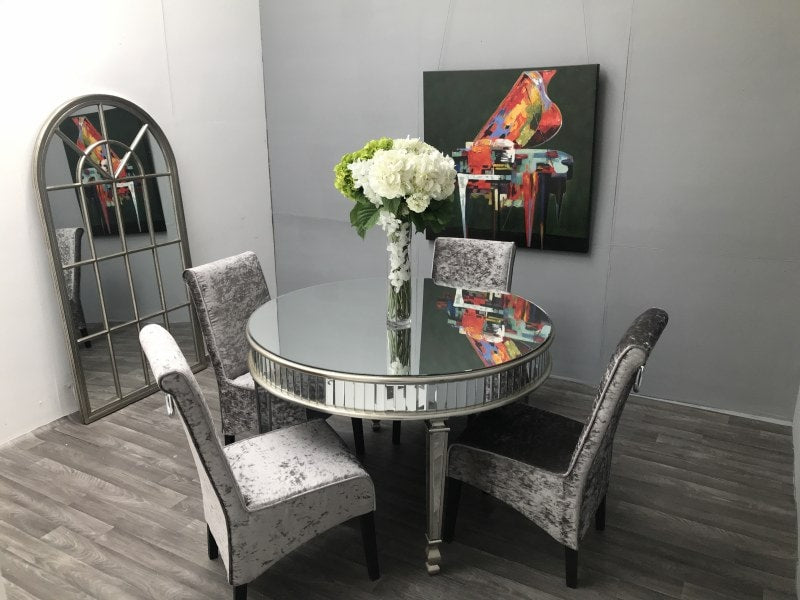 Round glass dining table with four chairs arranged around it.