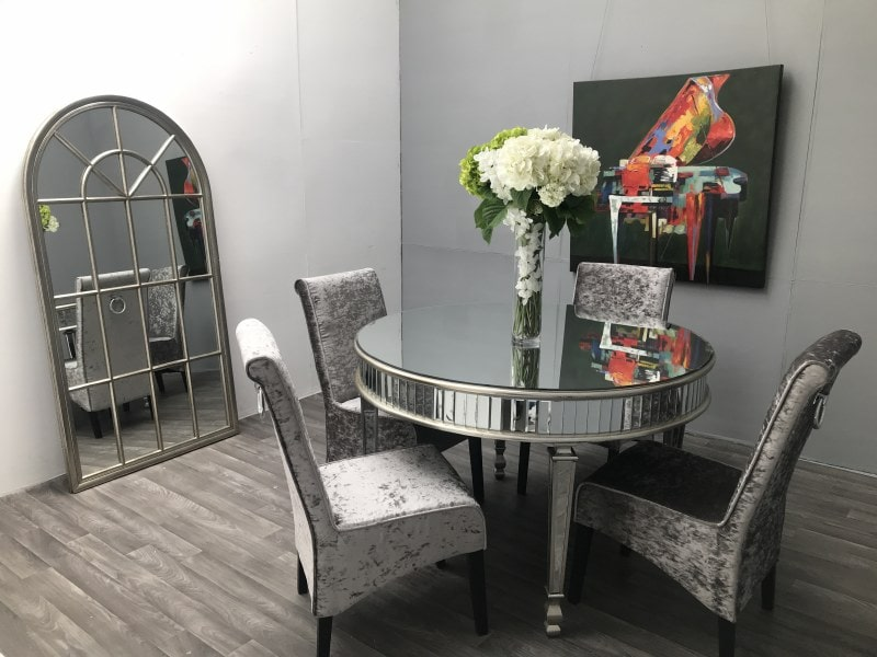 Round luxury mirrored dining table. Arranged in small room with four chairs around the table.
