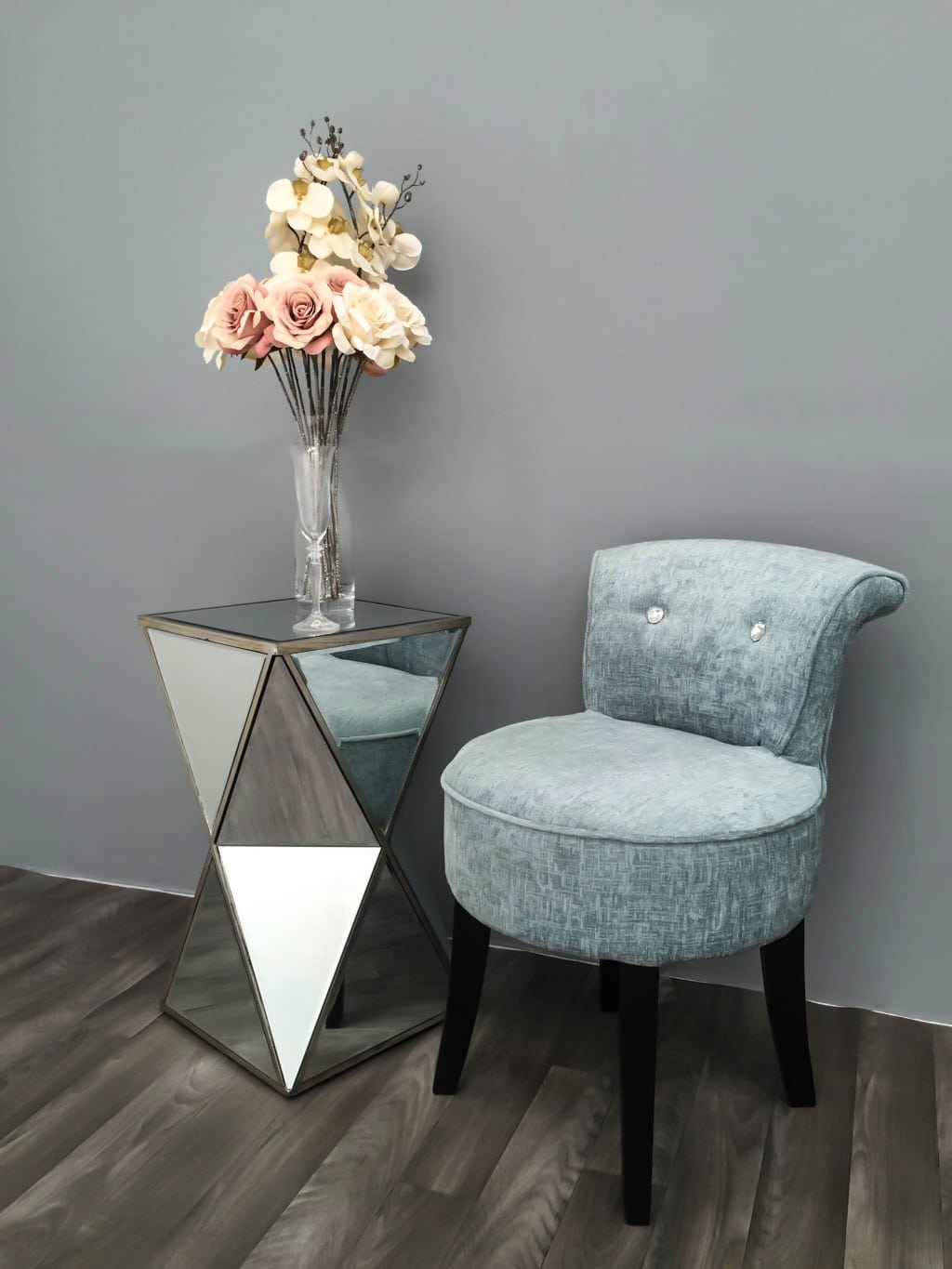 Mirrored Side Table arranged with flowers, glass vase and blue chair