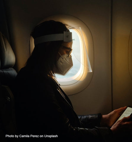 traveling, sitting in the dark airplane with mask