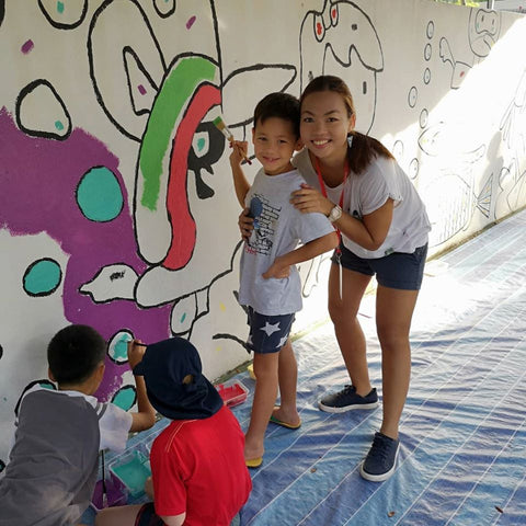 Mandy Maung and her son, Roco, painting a mural