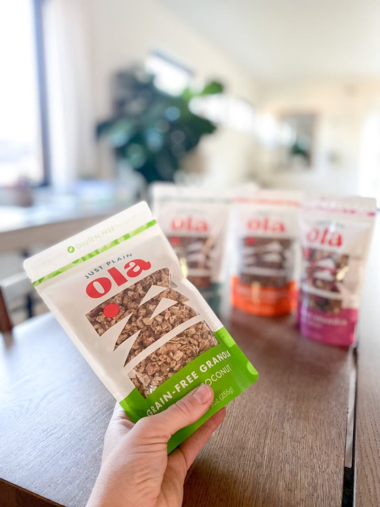 All four flavors of Just Plain Ola in 9oz bags: Toasted Coconut, Pumpkin Spice, Very Berry and Original Cinnamon