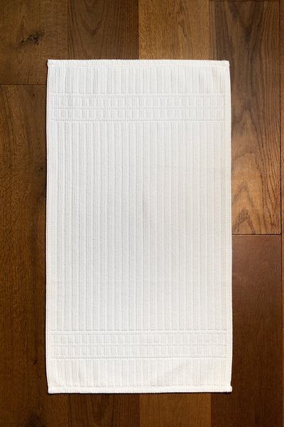 Madison Collection Canelado Bath Mat on Wood Floor