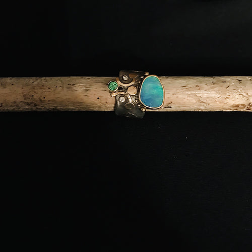 opal peridot and diamond ring with gold accents on a silver band