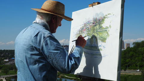 Adult painting outdoors with paint