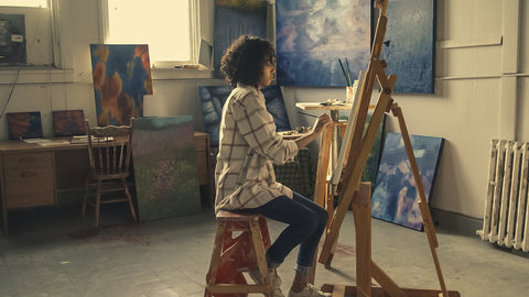 Adult woman sitting and painting with easel in clean room