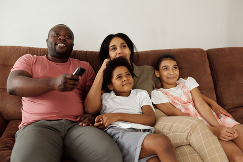 Family sitting on couch watching television