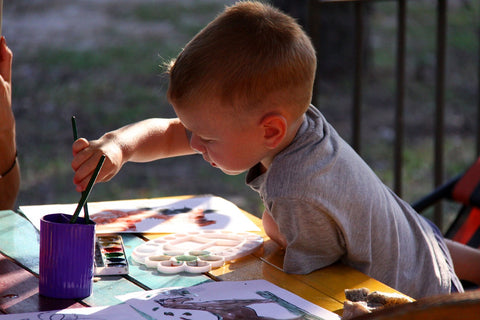Male Child Enjoying Painting On A Table With Lots of Colors
