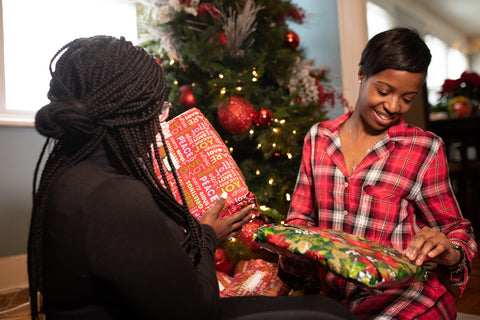 Woman giving each other personal gifts for christmas