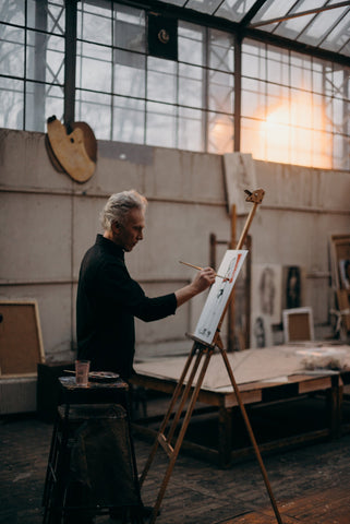 a painting master working in his workshop with paints