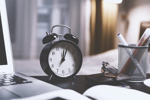 alarm clock on desk with office items